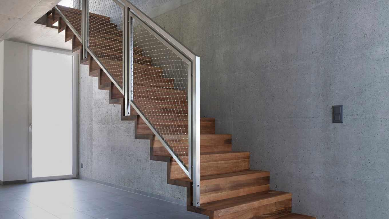 stainless steel safety railing on wooden stairs