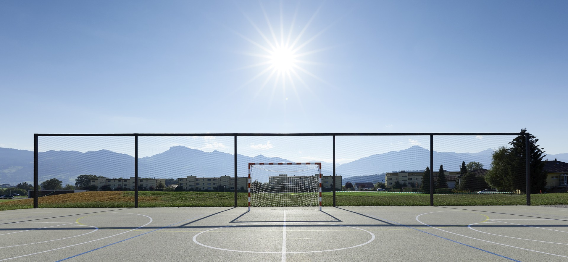 sports court with modern ball stop fence made of webnet