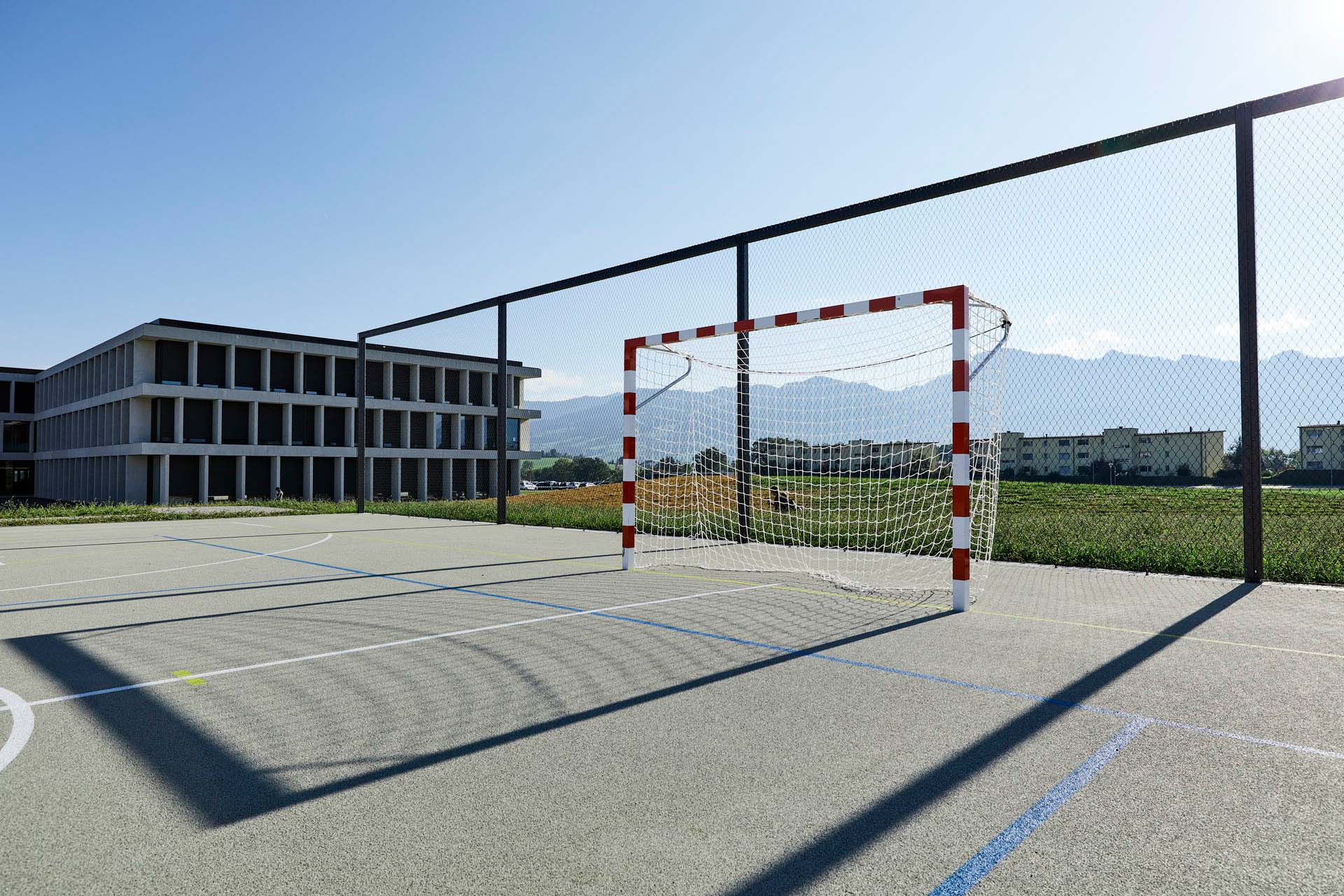 Sports court and goal in front of ball fence