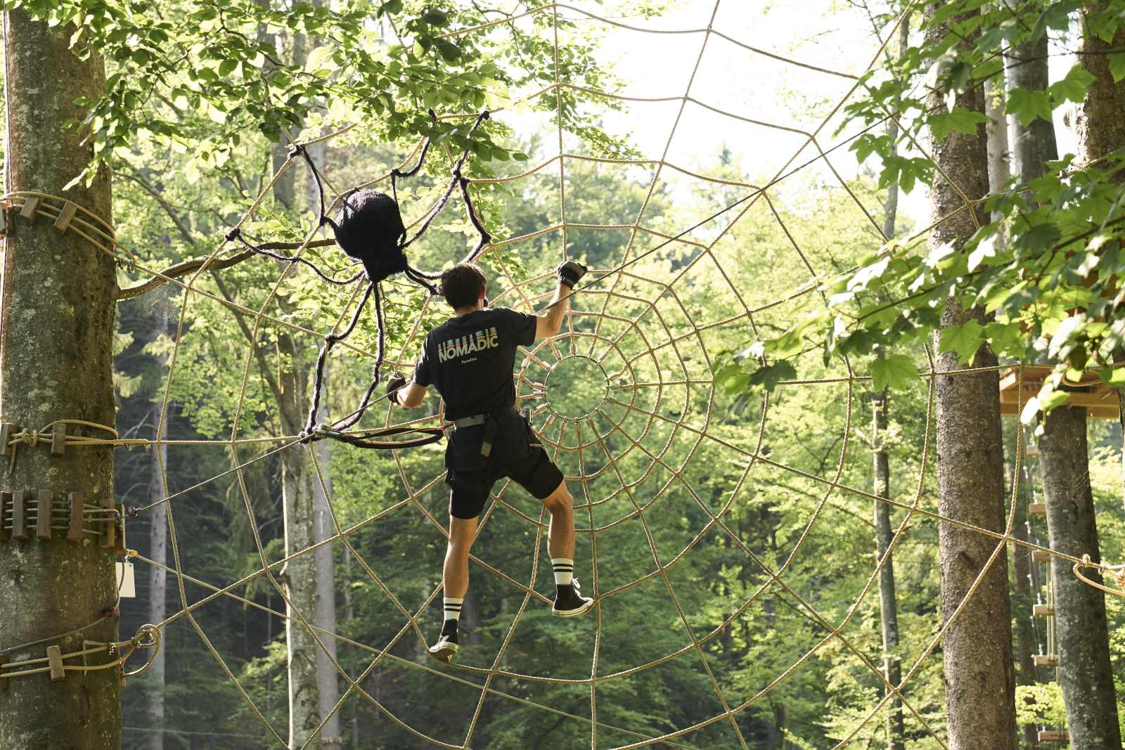 man climbing in spider web made of hemp ropes
