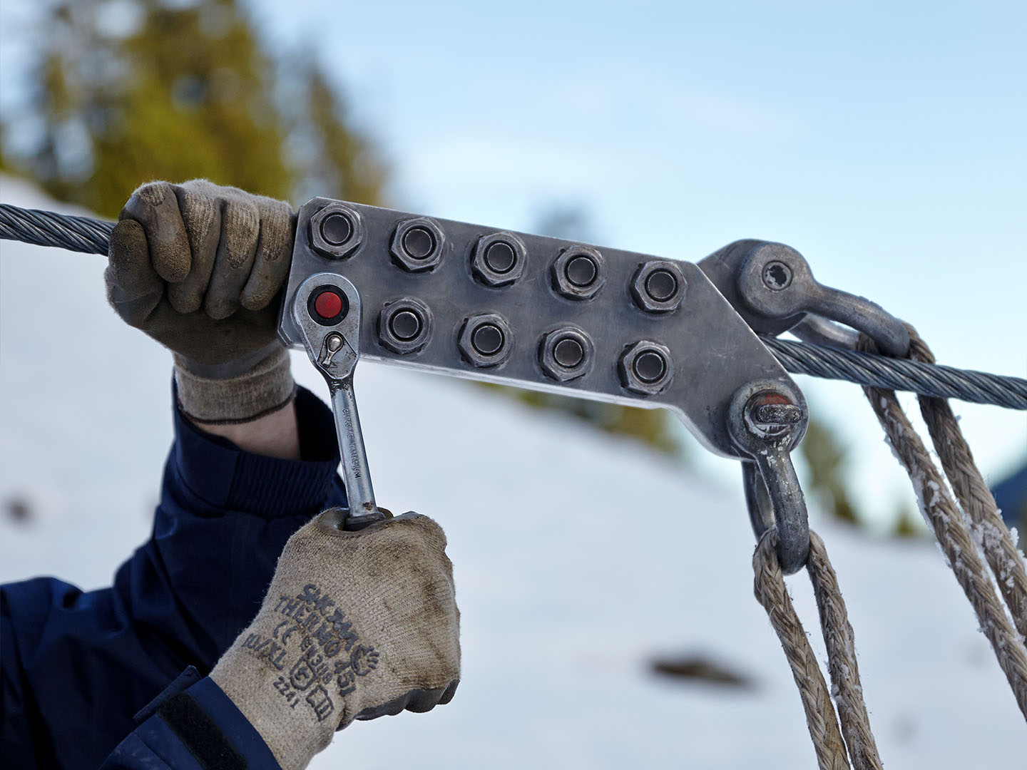 Two hands in gloves of a worker on a snowy mountain adjusting a cable clamp