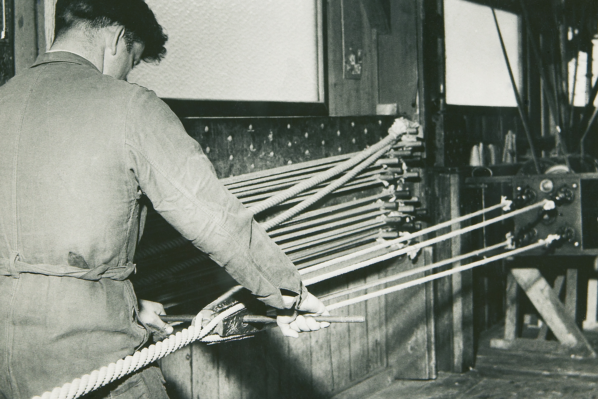 [Translate to Switzerland (CH), French (Default):] An old photography of a worker producing a fibre rope in the 1950s