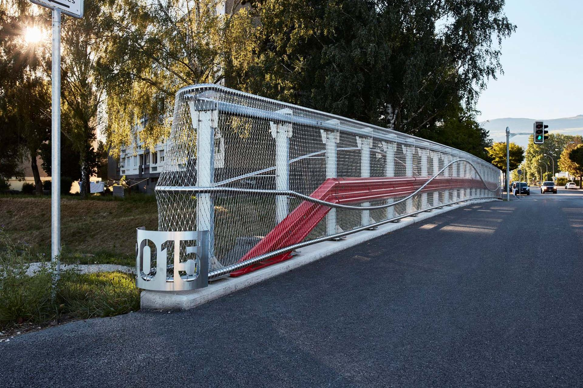 Webnet covers the railings on both sides of the bridge. It serves not only as a railing infill, but lets the striking red crash barriers and the curved steel railings shine.