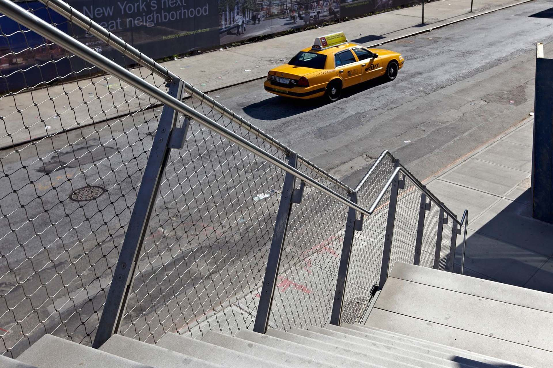 A yellow New York cab in front of a stair with a Webnet railing